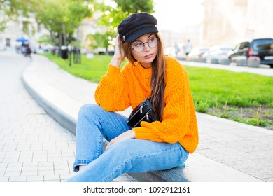 Outdoor lifestyle image of romantic   dreamy woman sitting on sidewalk and enjoying  evening . Wearing stylish jeans and orange sweater.