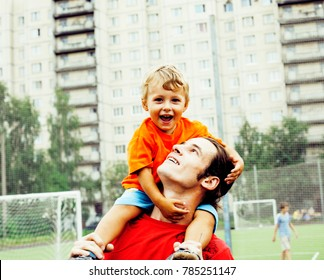 outdoor lifestyle people concept, happy family: father and son playing football together