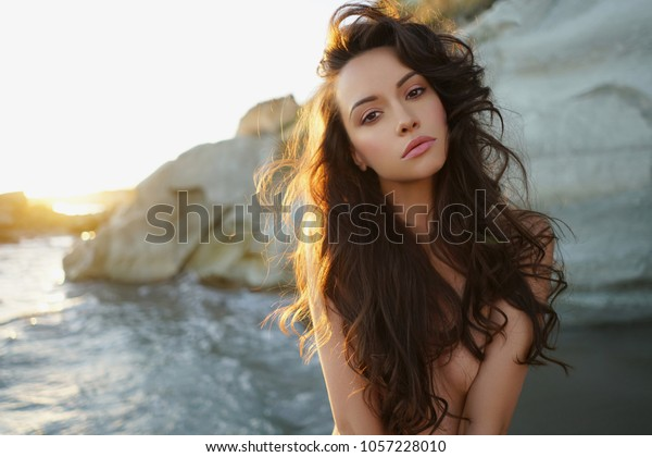 Outdoor lifestyle portrait of beautiful young brunette woman on the beach. Natural beauty. Travel and youth. Summer vibes