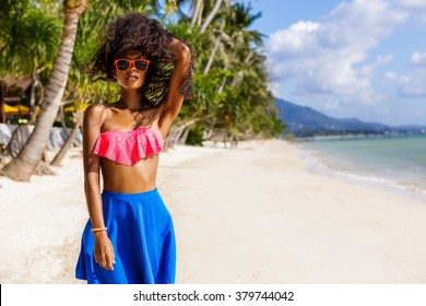 Outdoor lifestyle portrait of black beautiful teenage girl in bright outfit and sunglasses. Pretty hipster woman correct her curly hair. Sunny hot summer day at tropical beach with palms.
