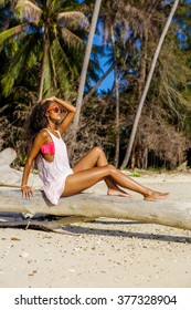 Outdoor lifestyle portrait of black sexy lady in pink bra and white t-shirt. Tanned hipster girl sit on dry palm tree. Sunny hot summer holiday day at tropical ocean beach with palms. Swag fashion.