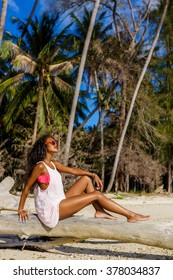 Outdoor lifestyle portrait of black sexy lady in pink bra and white t-shirt. Tanned hipster girl sit on dry palm tree. Sunny hot summer holiday day at tropical beach with palms. Swag fashion.