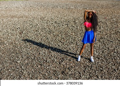 Outdoor lifestyle portrait of black sexy woman in blue skirt, pink bra and white sneakers. Tanned hipster girl with long healthy curved hairs posing at stones beach. Sunny hot summer holiday day.