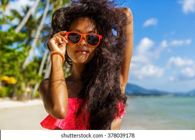 Outdoor lifestyle portrait of black sexy lady in pink bra. Tanned hipster woman smile and correct her bright sunglasses. Sunny hot summer day at tropical beach with palms. Swag. Wind in curly hair.