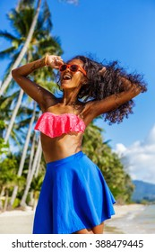 Outdoor lifestyle portrait of black sexy lady in pink bra and blue skirt. Pretty hipster woman correct her pink sunglasses. Sunny hot summer day at tropical beach with palms. Happy lady life.