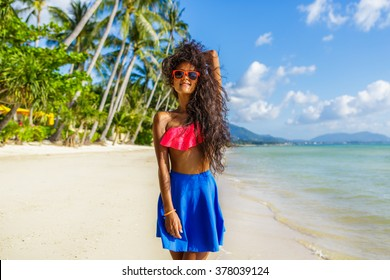 Outdoor lifestyle portrait of black teenage girl in pink bra and blue skirt. Young hipster woman smile and correct her long beautiful curly hair. Sunny hot summer day at tropical beach with palms.