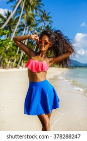 Outdoor lifestyle portrait of black teenage girl in pink bra and blue skirt. Young hipster woman correct her pink sunglasses and her curly hair. Sunny hot summer day at tropical beach with palms.