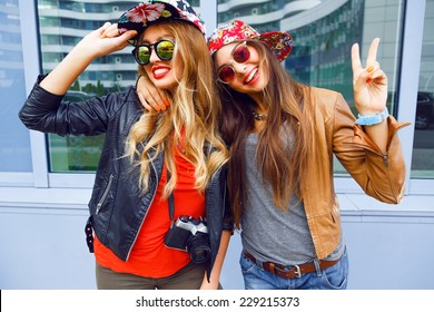 Outdoor lifestyle portrait of couple best friends pretty young girls, hugs making funny faces and laughing, wearing bright hipster swag outfits and leather jackets, urban background.