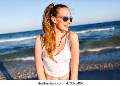 Outdoor lifestyle portrait of funny happy girl traveling to the ocean alone, smiling and enjoy sea beach time , happy positive emotions, mirrored sunglasses, white crop top and backpack, joy, motion.