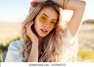 Outdoor lifestyle portrait of graceful  white woman standing on sunny beach near ocean . Wearing yellow glasses. Nature background.