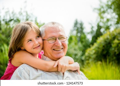 Outdoor lifestyle portrait of grandchild embracing grandfather