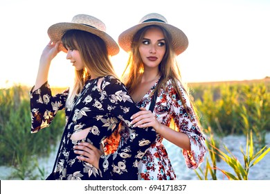 Outdoor lifestyle portrait pf happy best friend girl having fun on countryside vacation, wearing elegant boho dresses and hats, travel mood. Hugs on sunset, romantic atmosphere.
