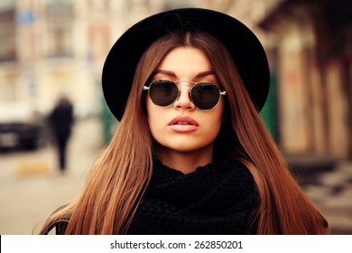 Outdoor lifestyle portrait of pretty funny hipster woman. Modern urban girl having fun. Beautiful young girl in a hat