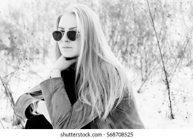 Outdoor lifestyle portrait of pretty hipster blonde woman. Modern urban girl bw image. Black and white photo.