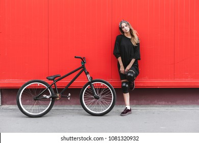 Outdoor lifestyle portrait of pretty sexy young girl in hockey jersey style dress posing with street bicycle