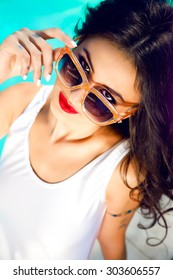 Outdoor lifestyle portrait of pretty sexy women on vacation ,wearing bright bikini and sunglasses,relax and having fun at pool party. Making funny surprised face.red lips,summer colors,toned