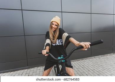 Outdoor lifestyle portrait of pretty sexy young girl in hockey jersey style dress sitting on street bicycle