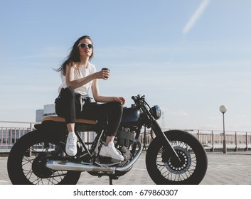 Outdoor lifestyle portrait of sexy biker girl sitting on a vintage custom motorcycle and drinking coffee