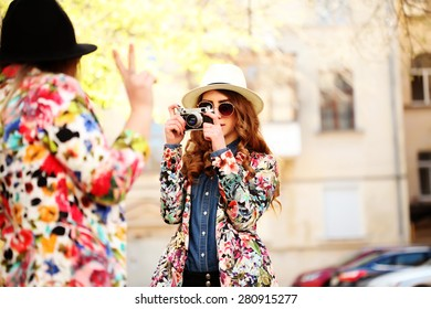Outdoor lifestyle portrait of two best friends hipsters making photo on their vintage camera, having fun together, joy and happiness, wearing trendy bright clothes caps and sunglasses.
