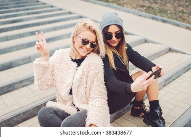 Outdoor lifestyle portrait of two best friends, smiling and having fun together, enjoy eachother company posing and makingselfie pictures to eachother and share happiness