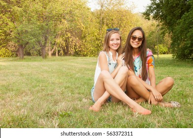 Outdoor lifestyle portrait of two best friends hipster girls wearing stylish bright outfits, t-shirts, denim shorts and glasses, going crazy and having great time together
