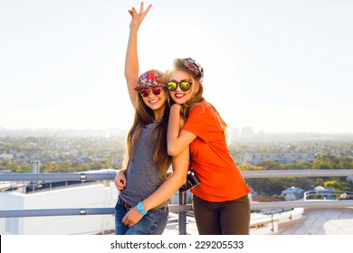 Outdoor lifestyle portrait of two young girl posing at the roof, amazing view on the city, evening sunlight freedom mood. Wearing bright casual clothes swag hats and mirrored sunglasses.
