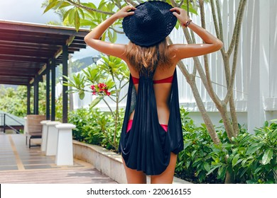 Outdoor lifestyle portrait of woman relaxed at resort on her vacation in hot tropical county, posing at exotic garden, wearing hat, bikini, and black cover.