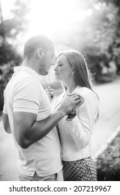 Outdoor lifestyle portrait of young couple in love standing in old town on the street behind sunset