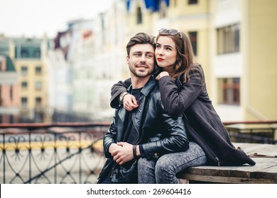 Outdoor lifestyle portrait of young couple in love  in old town on the street, couple sitting, city, europe