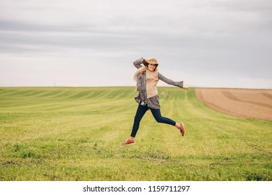 Outdoor lifestyle portrait of young happy woman posing in countryside