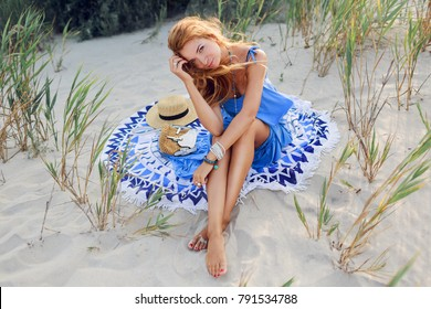 Outdoor lifestyle portrait of young smiling woman in stylish summer blue beach dress  sitting  on towel on sunny ocean coast.
