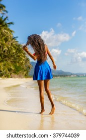 Outdoor lifestyle of a sporty black teenage girl with long beautiful legs at tropical seashore. Close-up detail of female feet, water splash and golden sand. Young hipster, sunny hot summer day.