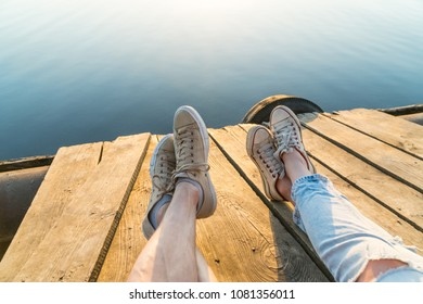 Outdoor lifestyle view of a couple wearing sneakers sitting on a wooden pier at the water on a sunset