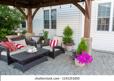 Outdoor living space on a brick patio with covered gazebo and comfortable furniture with colorful striped cushions