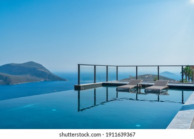 Outdoor lounge area of a luxury villa with a view of the Mediterranean sea. Summer vacation at poolside. above the sea