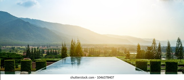 Outdoor luxury swimming pool at the holiday, background is beautiful mountain, relax place.