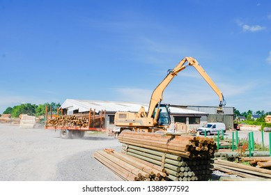 Outdoor machine lift up stacking the logs at sawmill in europe with background green forest ,blue sky and clouds. industrial wood yard with stacks of new wood poles.