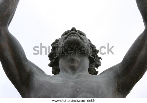 outdoor male statue reaching skyward