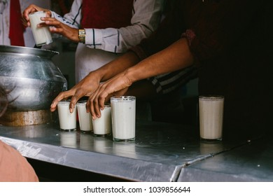 Outdoor market, hands of sellers holding Lassi, traditional nepali yogurt drink. Street food in Asia