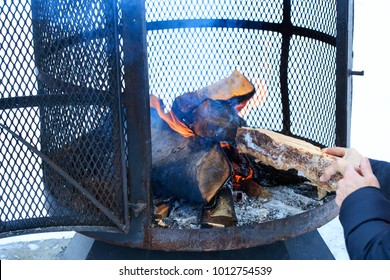 Outdoor metallic fireplace in winter season charged with firewood, in the burning process. Wood-burning fire pit with removable fire pan and with wide bar ribs and handles.