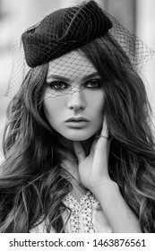 Outdoor monochrome close up retro, vintage fashion portrait of young elegant woman wearing hat with veil posing in street. Model with beautiful long hair.