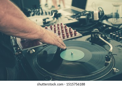 Outdoor music party. Dj playing on vinyl. Dj's hands and turntable close up, blurred people on the background
