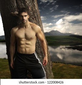 Outdoor natural portrait of a gorgeous male fitness model