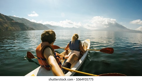 Outdoor Nature Selfie of Young Lovely Couple Canoeing Kayaking on Sunny Day on Lake Sea with Mountain View Background. Best Friends Enjoying and Having Fun Together on Kayak in Vacation Holiday Trip.