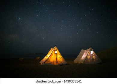 Outdoor night camping, Milky Way, stars. Outside the city, relaxing with friends in nature. the tent glowing from inside . Camp in the desert. Five Billion stars resort