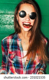 Outdoor night closeup lifestyle urban style portrait of pretty young beautiful girl with smile and chocolate in her mouth with red lipstick having fun