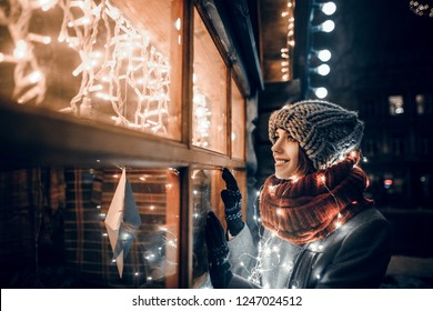 Outdoor night photo of young beautiful happy smiling girl looking through shop window with festive decoration, posing in Christmas fair, in street of european city, wearing knitted beanie hat, scarf