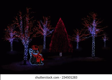 Outdoor night shot of Illuminated trees and Snowman for the perfect Christmas atmosphere