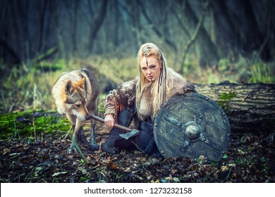 Outdoor northern warrior woman with braided hair and war makeup holding shield and ax with wolf next to her ready to attack - Movie theme of woman warrior viking in forest - Cinematic and movie filter