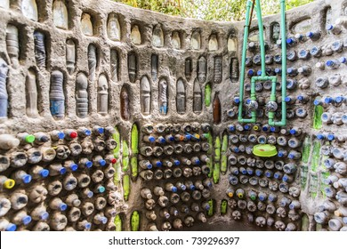 Outdoor, open-air shower room wall, handmade using mud filled PET plastic bottles as bricks. Recycled containers. Abstract innovative design, low cost, eco friendly, green, sustainable construction.
